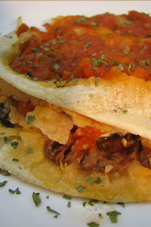 stacked black bean tortillas with tomato sauce