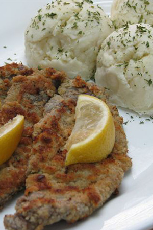 pan fried wiener schnitzel with lemon wedges and Hungarian mashed potatoes